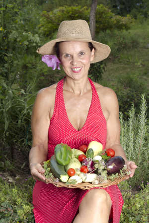 Mid age smilling woman with straw hat, showing  fresh vegetables  in her garden, on sunny summer afternoon photo