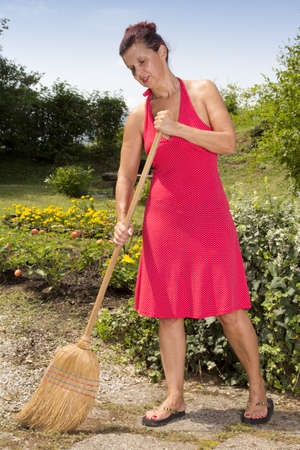 brooming: Cute mid age woman brooming the garden path with traditional  sorghum broom, on sunny afternoon Stock Photo