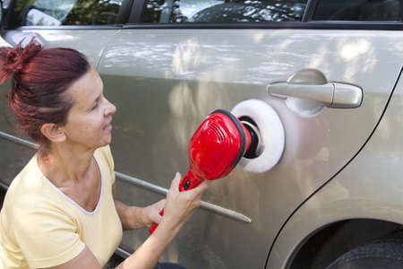 Mid aged cute woman polishing her car with electric polishing tool photo