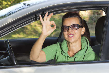 Friendly  woman looking out of car, indicating ok sign with her fingers  photo