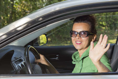 Friendly  woman looking out of car and waving hand at You photo