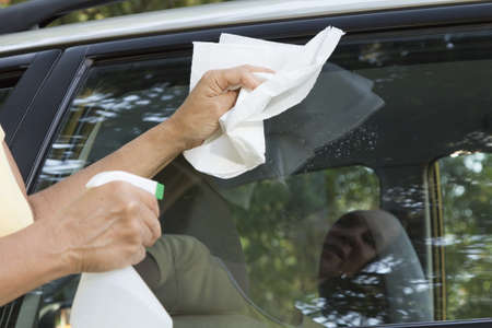 Cleaning the car window with paper towel, close up  photo