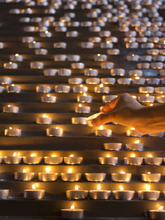 enlightening: Lighting candles in a church  Stock Photo