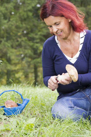 Cute smiling woman cleaning mushroom Boletus Edulis, on sunny autumn afternoon photo