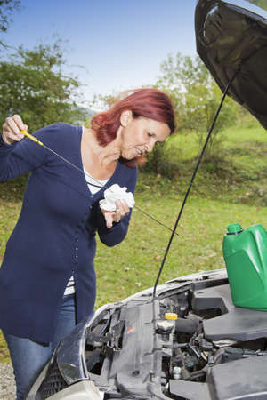 Cute woman driver checking level of oil on a car engine dipstick  photo