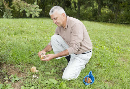 Happy smiling man cleaning mushroom Boletus Edulis, on sunny autumn afternoon under pine tree photo