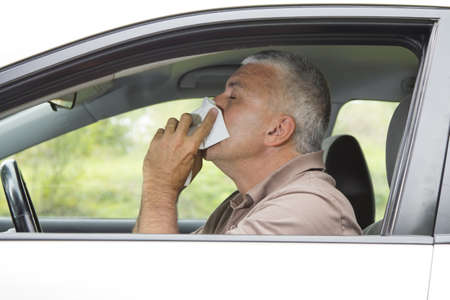 Sneezing man in the car having cold