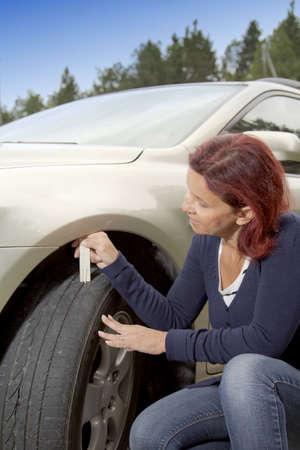 depth measurement: Woman driver measuring tyre profile on car tyre