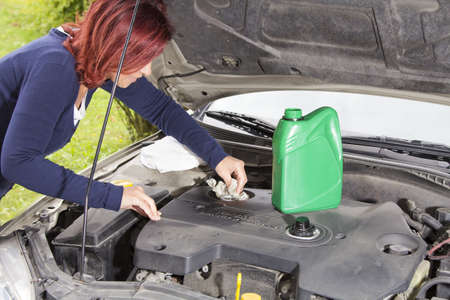 Car maintenance-Woman is cleaning car motor cover after adding oil photo