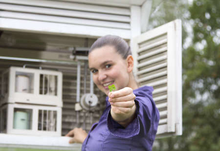 fourleaf: Smiling woman meteorologist shows four-leaf clover for luck- selective focus Stock Photo