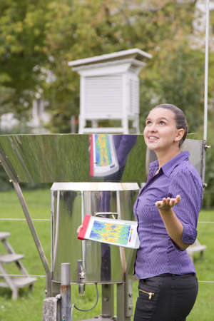 expects: Young woman meteorologist expects rain whilst inspecting instruments Stock Photo