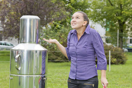 anemometer: Young woman meteorologist expects rain whilst inspecting instruments Stock Photo