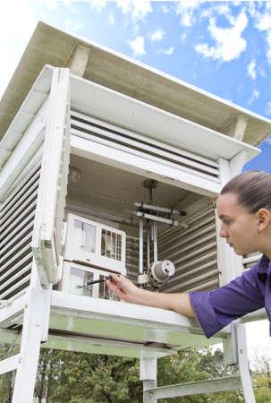 Meteorólogo Mujer joven que lee los instrumentos meteorológicos