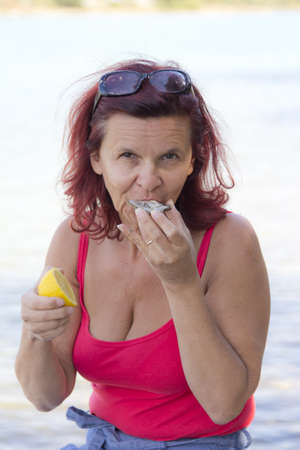 eroticism: Cute woman eating fresh oyster with fresh organic lemon