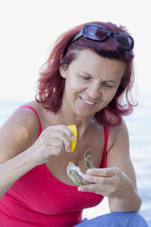 eroticism: Cute smiling woman eating fresh oyster with fresh organic lemon Stock Photo