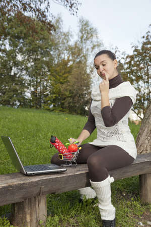 Concept of online shopping - cute girl thinks what to shop online- with notebook and shopping trolley photo