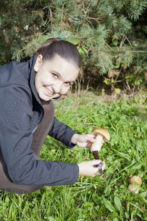 Cute smiling girl cleaning mushroom Boletus Edulis, on sunny autumn afternoon photo