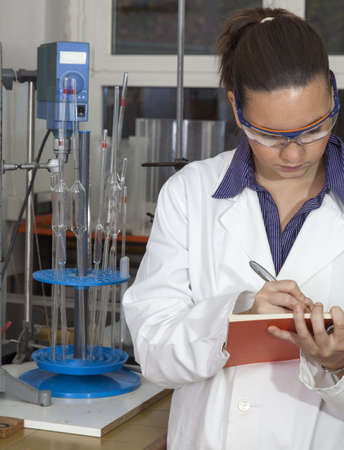 Cute female medical   scientific researcher writing notes whilst working  in a laboratory Stock Photo - 16119183
