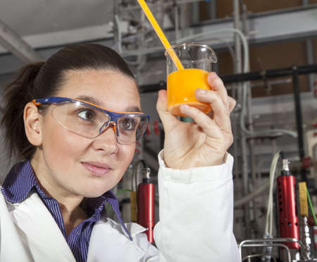 Closeup of a cute smiling female researcher holding test beaker and tube with chemicals, while carrying out some experiments in a laboratory, focus on liquid in test tube Stock Photo - 16119173