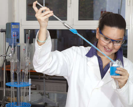 Closeup of a cute female researcher holding test beaker and tube with chemicals, while carrying out some experiments in a laboratory, focus on liquid in test tube Stock Photo - 16119171