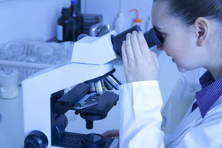 Cute smiling female medical   scientific researcher using her microscope in a laboratory Stock Photo - 16119176