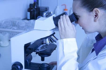 Cute smiling female medical   scientific researcher using her microscope in a laboratory Stock Photo - 16119176