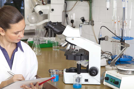 Cute female medical   scientific researcher writing notes whilst using her microscope in a laboratory Stock Photo - 16119177