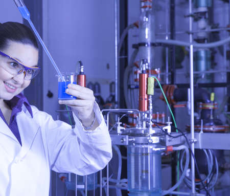 Closeup of a cute female researcher holding test beaker and tube with chemicals, while carrying out some experiments in a laboratory, focus on liquid in test tube, blue color toned image photo