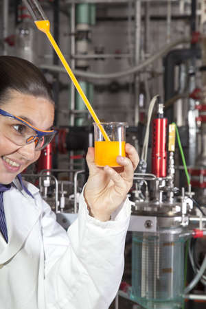 Closeup of a cute smiling female researcher holding test beaker and tube with chemicals, while carrying out some experiments in a laboratory, focus on liquid in test tube photo
