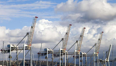 Port cargo cranes over blue cloudy sky background  photo