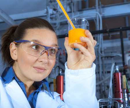 Female researcher holding test beaker-BACKGROUND BLUE TONED Stock Photo - 16143467