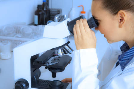 Female medical   scientific researcher using her microscope -BACKGROUND BLUE TONED