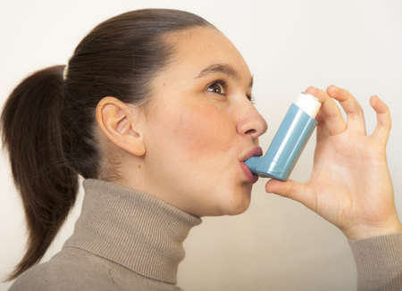 Cute young female using an asthma inhaler for preventing attacks