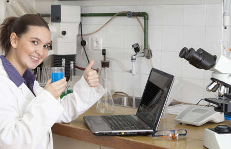 Cute female researcher showing OK sign, while carrying out some experiments in a laboratory photo