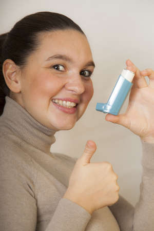 Girl with asthma inhalator shows OK sign photo