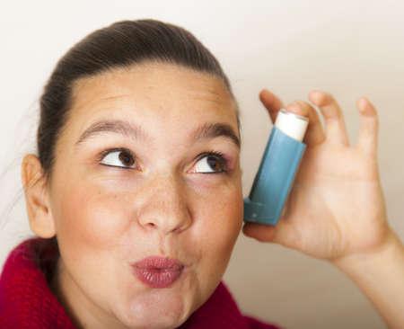 bronchial: Smiling girl holds asthma inhalator against her ear