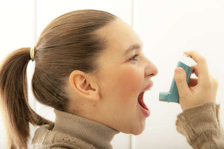 Cute young female start using an asthma inhaler for preventing attacks  Stock Photo