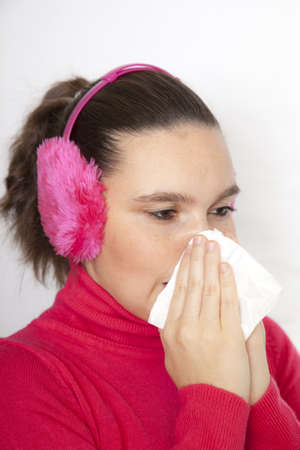 Cute young woman with earmuffs, who has caught cold, using handkerchief, whilst sneezing photo
