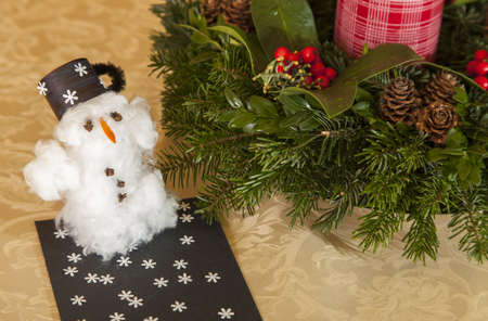 cottonwool: Cottonwool snowman on the table near the Christmas garland Stock Photo