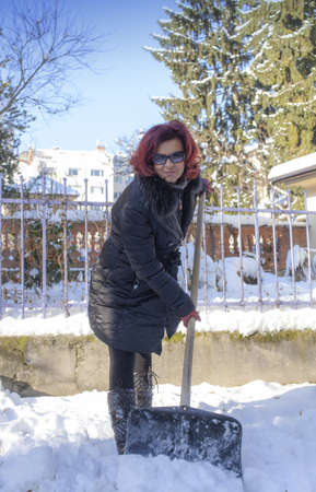 Woman shoveling snow off sidewalk photo