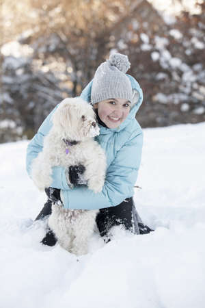 Smiling cute girl outdoors in the park playing with her dog, on sunny winter day photo
