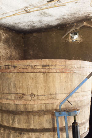 mustiness: Big vintage wood barrel and old bottle corking machine in traditional wines cellar Stock Photo