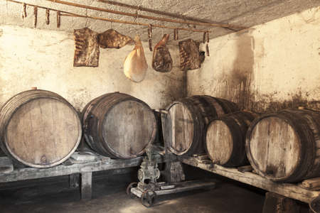 Interior of very old wine cellar with vintage wine pump and dried meat delicatessen
