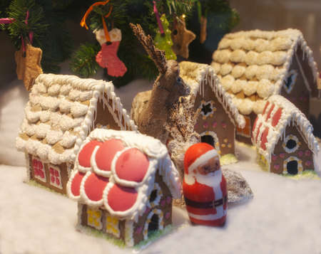 Beautiful homemade gingerbread village, with dear and Santa against Christmas tree decoration, glamour effect, selective focus on center of village Stock Photo - 17080526