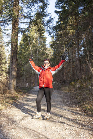 nordic country: Sportive woman waving hello whilst Nordic walking cross country in the mountain forest Stock Photo