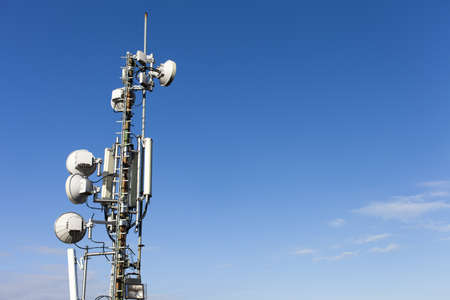 Telecommunication mast with microwave link antennas over a blue sky - space for Your text