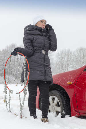 Cute girl using phone and calling for help on snowy winter day photo