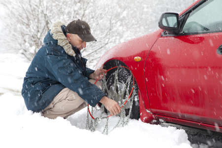 Mid aged male driver mounting car tyre chains on very snowy road