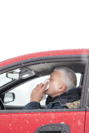 Mid aged man with flu symptoms sneezes in a car on snowy  winter day  Using handkerchief closes mouth with his hands  Stock Photo - 17381658