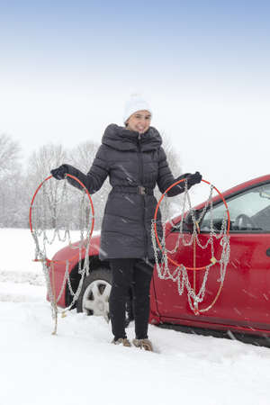 Cute female driver holding tyre chains on snowy winter day and waiting for help photo